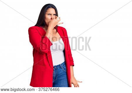 Young beautiful brunette woman wearing elegant clothes smelling something stinky and disgusting, intolerable smell, holding breath with fingers on nose. bad smell
