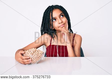 Young african american girl child with braids holding chickpeas bowl serious face thinking about question with hand on chin, thoughtful about confusing idea