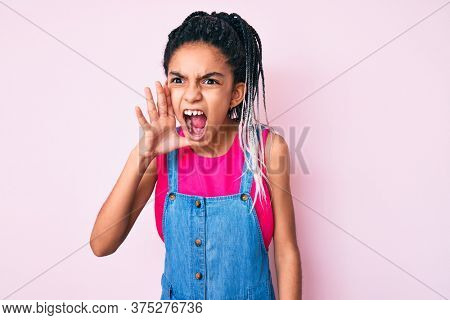 Young african american girl child with braids wearing casual clothes over pink background shouting and screaming loud to side with hand on mouth. communication concept.