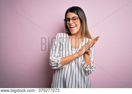 Young beautiful woman wearing casual striped t-shirt and glasses over pink background clapping and applauding happy and joyful, smiling proud hands together