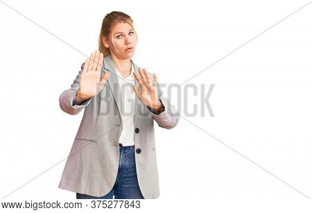 Young beautiful blonde woman wearing elegant jacket moving away hands palms showing refusal and denial with afraid and disgusting expression. stop and forbidden.