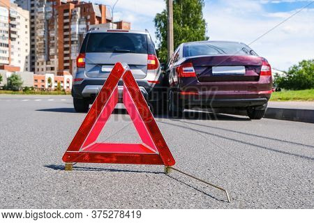 Triangular Red Retro-reflective Sign Of Accident On The Road. Collision Of Two Cars. Broken Bumper A