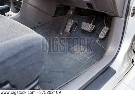 Gray Cloth Car Mat In The Interior Of A Japanese Sedan With Three Pedals Gas, Brake And Clutch In A