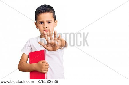 Little cute boy kid reading a book with open hand doing stop sign with serious and confident expression, defense gesture