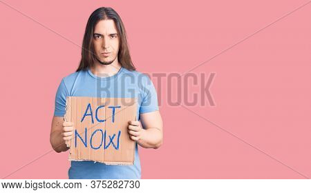 Young adult man with long hair holding act now banner thinking attitude and sober expression looking self confident
