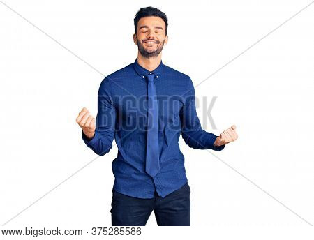 Young handsome hispanic man wearing business clothes very happy and excited doing winner gesture with arms raised, smiling and screaming for success. celebration concept.