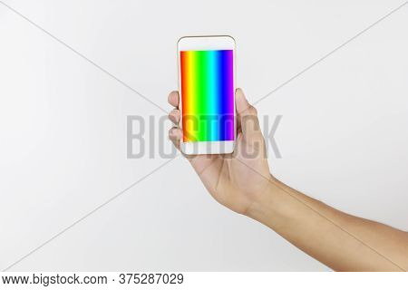 Hand Man Holding Mobile Phone In Screen Show Lgbt Symbols. Hand Hold Smart Phone With Rainbow Screen