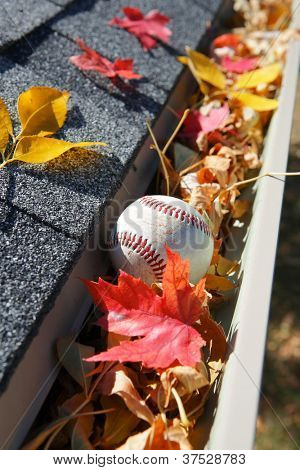 Rain gutter full of autumn leaves and a baseball