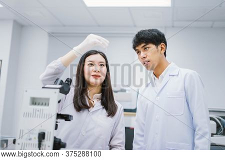 Two Young Medical Scientist Looking At Test Tube In Medical Laboratory , Select Focus On Male Scient