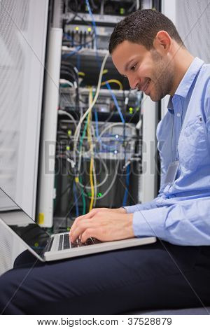 Man using laptop in front of servers in data center