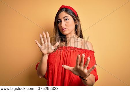Young beautiful woman colorful summer style over yellow isolated background Moving away hands palms showing refusal and denial with afraid and disgusting expression. Stop and forbidden.