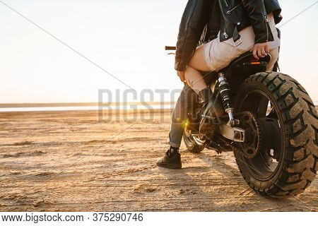 Back view of a young stylish couple enjoying ride on a motorbike at the beach