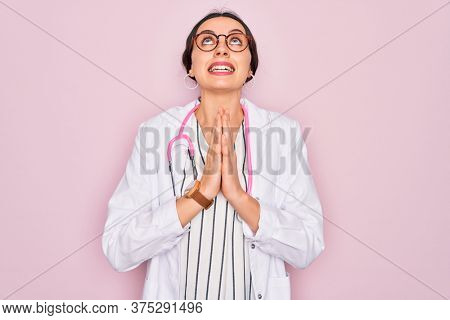 Beautiful doctor woman with blue eyes wearing coat and stethoscope over pink background begging and praying with hands together with hope expression on face very emotional and worried. Begging.