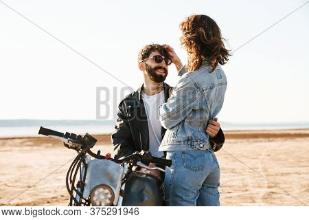 Attractive young happy couple embracing while leaning on a motorbike at the sunny beach