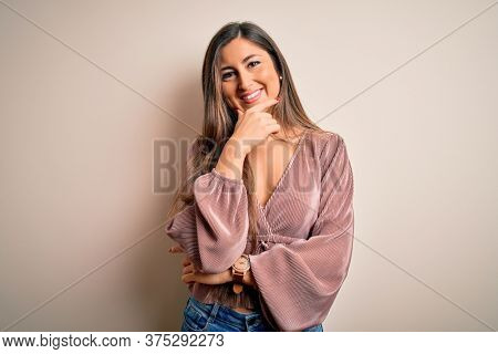 Young beautiful brunette elegant woman with long hair standing over isolated background looking confident at the camera smiling with crossed arms and hand raised on chin. Thinking positive.
