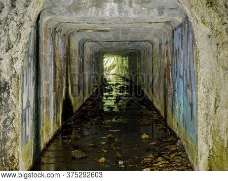 Davenport, California - July 5, 2020: Abandoned Ocean Shore Railroad Creek Tunnel, Drainage Of Yello