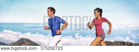 Sport runners athletes running on mountain trail run outside in panoramic banner nature. Fit young sport multiracial fitness couple training cross country running together. Asian woman, Caucasian man.
