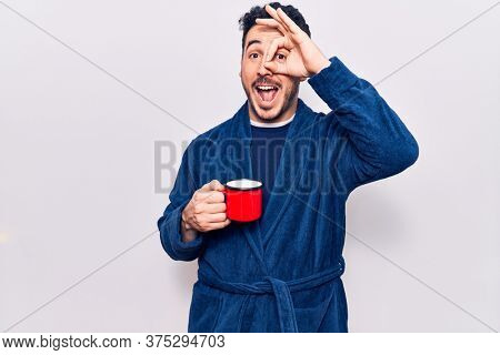 Young hispanic man wearing robe holding coffee smiling happy doing ok sign with hand on eye looking through fingers
