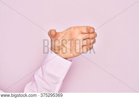 Hand of caucasian young man showing fingers over isolated pink background holding invisible object, empty hand doing clipping and grabbing gesture