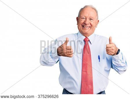 Senior handsome grey-haired man wearing elegant tie and shirt success sign doing positive gesture with hand, thumbs up smiling and happy. cheerful expression and winner gesture.