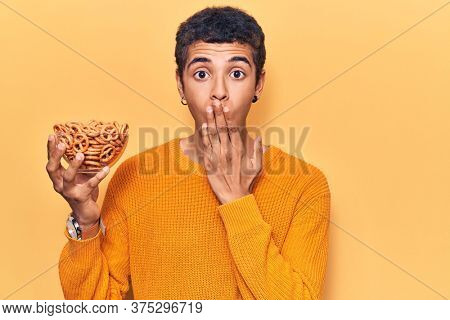 Young african amercian man holding pretzels covering mouth with hand, shocked and afraid for mistake. surprised expression
