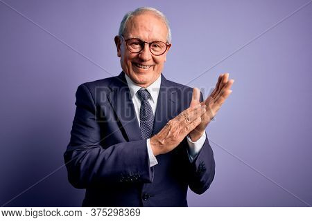 Grey haired senior business man wearing glasses and elegant suit and tie over purple background clapping and applauding happy and joyful, smiling proud hands together