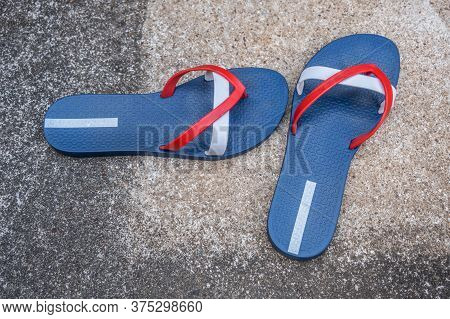 A Pair Of Red White And Blue Flip-flops Left On The Cement Patio By The Poolside On A Hot Summer Day