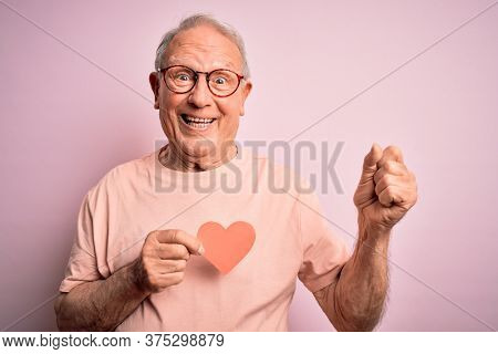 Senior grey haired man holding heart shape paper over pink background screaming proud and celebrating victory and success very excited, cheering emotion