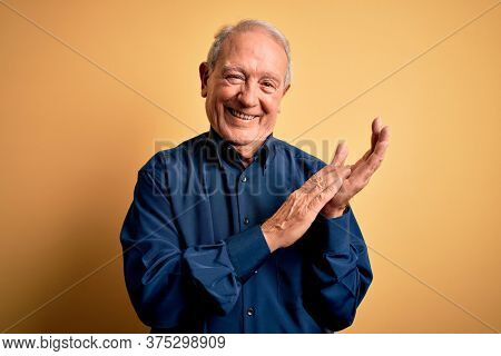 Grey haired senior man wearing casual blue shirt standing over yellow background clapping and applauding happy and joyful, smiling proud hands together