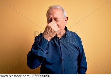 Grey haired senior man wearing casual blue shirt standing over yellow background smelling something stinky and disgusting, intolerable smell, holding breath with fingers on nose. Bad smell