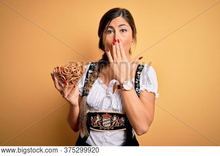 Young brunette german woman wearing traditional Octoberfest dress holding bowl with pretzels cover mouth with hand shocked with shame for mistake, expression of fear, scared in silence, secret concept