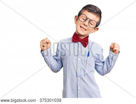 Cute blond kid wearing nerd bow tie and glasses very happy and excited doing winner gesture with arms raised, smiling and screaming for success. celebration concept.