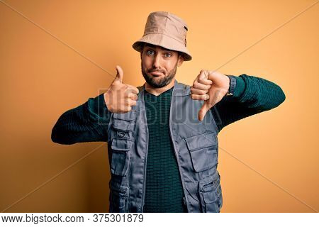 Handsome tourist man with beard on vacation wearing explorer hat over yellow background Doing thumbs up and down, disagreement and agreement expression. Crazy conflict