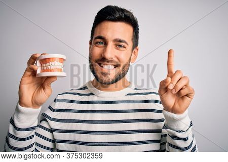 Young handsome man with beard holding plastic denture teeth over white background pointing finger up with successful idea. Exited and happy. Number one.