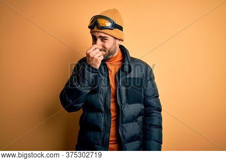 Young handsome skier man with beard wearing snow sportswear and ski goggles smelling something stinky and disgusting, intolerable smell, holding breath with fingers on nose. Bad smell