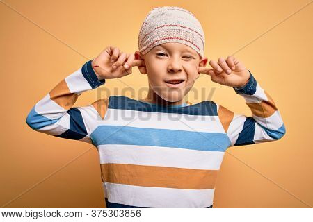 Young little caucasian kid injured wearing medical bandage on head over yellow background covering ears with fingers with annoyed expression for the noise of loud music. Deaf concept.