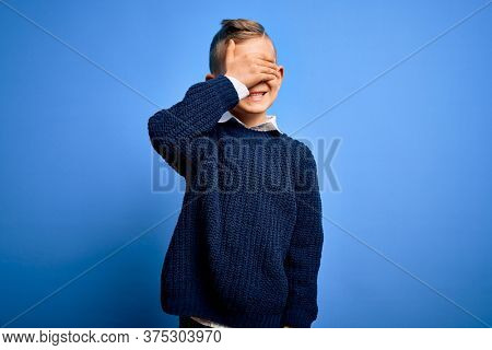 Young little caucasian kid with blue eyes wearing winter sweater over blue background smiling and laughing with hand on face covering eyes for surprise. Blind concept.