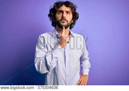 Young handsome business man with beard wearing shirt standing over purple background Thinking concentrated about doubt with finger on chin and looking up wondering