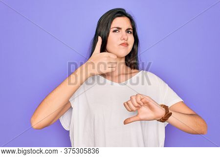 Young beautiful brunette woman wearing casual white t-shirt over purple background Doing thumbs up and down, disagreement and agreement expression. Crazy conflict