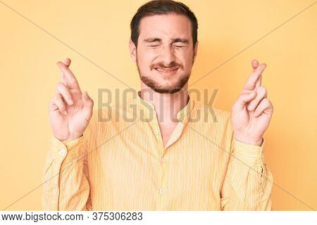 Young handsome man wearing casual clothes gesturing finger crossed smiling with hope and eyes closed. luck and superstitious concept.