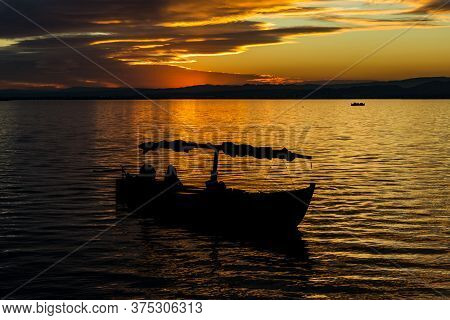 Silhouette Of A Small Traditional Boat At Dusk In The Albufera In Valencia, A Freshwater Lagoon And