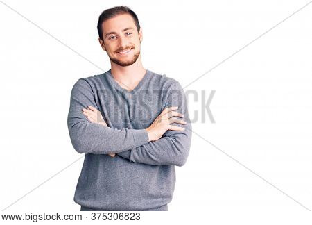 Young handsome caucasian man wearing casual winter sweater happy face smiling with crossed arms looking at the camera. positive person.