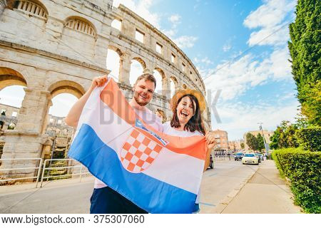 Happy Beautiful Couple In Front Of Coliseum In Pula Croatia With Croatian Flag