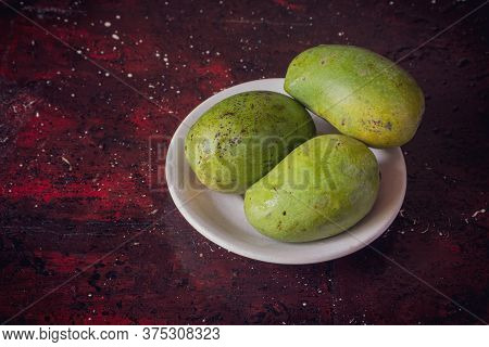 Ripe Mangoes In A Plate Isolated On Reddish Background With Copy Space For Texts Writing
