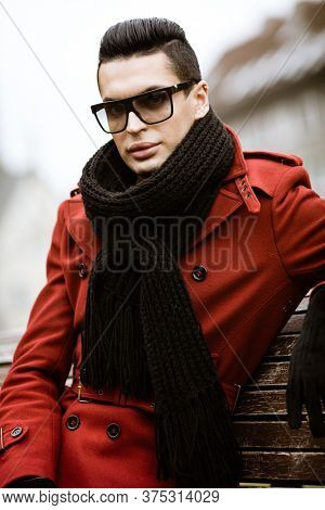 LGBTQ community lifestyle concept. Young homosexual man sits on bench in city park. Handsome fashionable gay male model poses in cityscape outdoors. Wears red coat, gloves, sunglasses and black scarf.