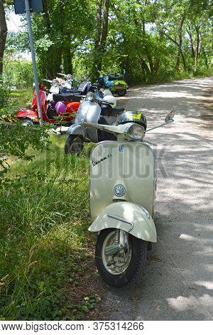Villaggio Di Punta Sdobba, Italy - June 14 2020. Seven Vespas, Part Of A Small Rally Of Vespa Motori