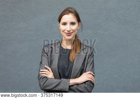 A Young Handsome Woman Is Standing In A Grey Business Suit On The Background Of An Office Building.