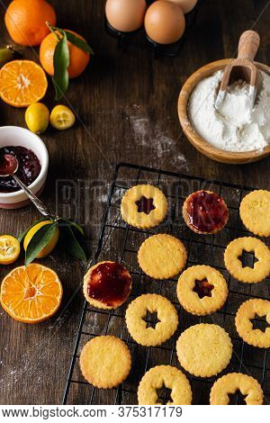 Christmas Baking, Traditional Linzer Cookies With Orange And Berry Jam On Wooden Table