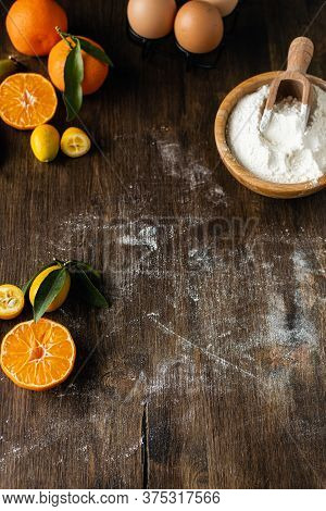 Homemade Christmas Baking Background, Wooden Table With Flour, Eggs And Tangerines