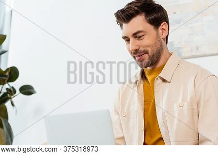 Selective Focus Of Handsome Teleworker Using Laptop At Home